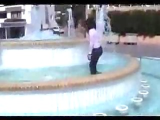 Marjorie is getting wet in a public fountain -